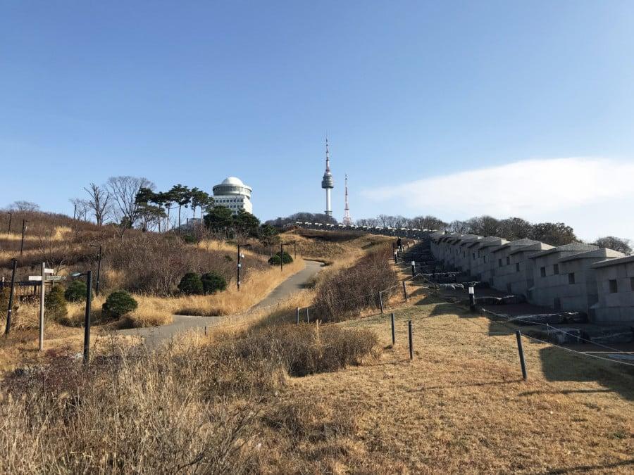 Südkorea | Sehenswürdigkeiten & interessante Orte: Fußweg zum N-Seoul Tower. Blick auf einen Weg durch den Namsan Park bei blauem Himmel mit dem Turm im Hintergrund