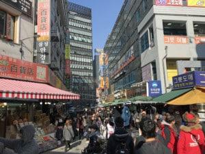 Südkorea | Seoul, Namdaemun Market. Blick auf eineGase mit Marktständen und Menschen beim Shoppen
