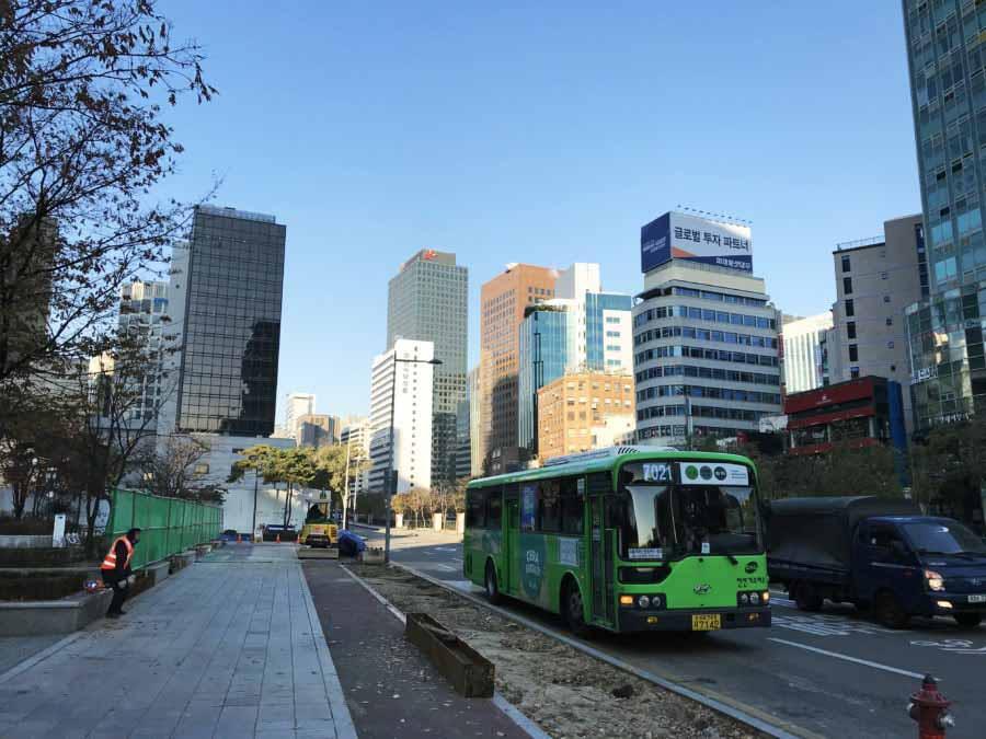 Südkorea | Typischer Stadtbus in Seoul. Blick auf einen grünen modernen Bus mit den Hochhäusern der Stadt im Hintergrund bei blauem Himmel