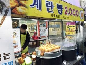 Südkorea | Typisches Street Food in Seoul: Egg Bun. Blick auf den Stand und seinen Verkäufer der Eierspeise