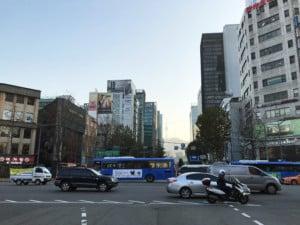 Sonnenuntergang in der Innenstadt mit dem N-Seoul Tower im Hintergrund. Blick auf eine Straße mit fahrenden Autos und Hochhäuser