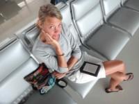 Karin am Flughafen auf Phu Quoc in Vietnam, den Kindle lesend mit Blick nach oben
