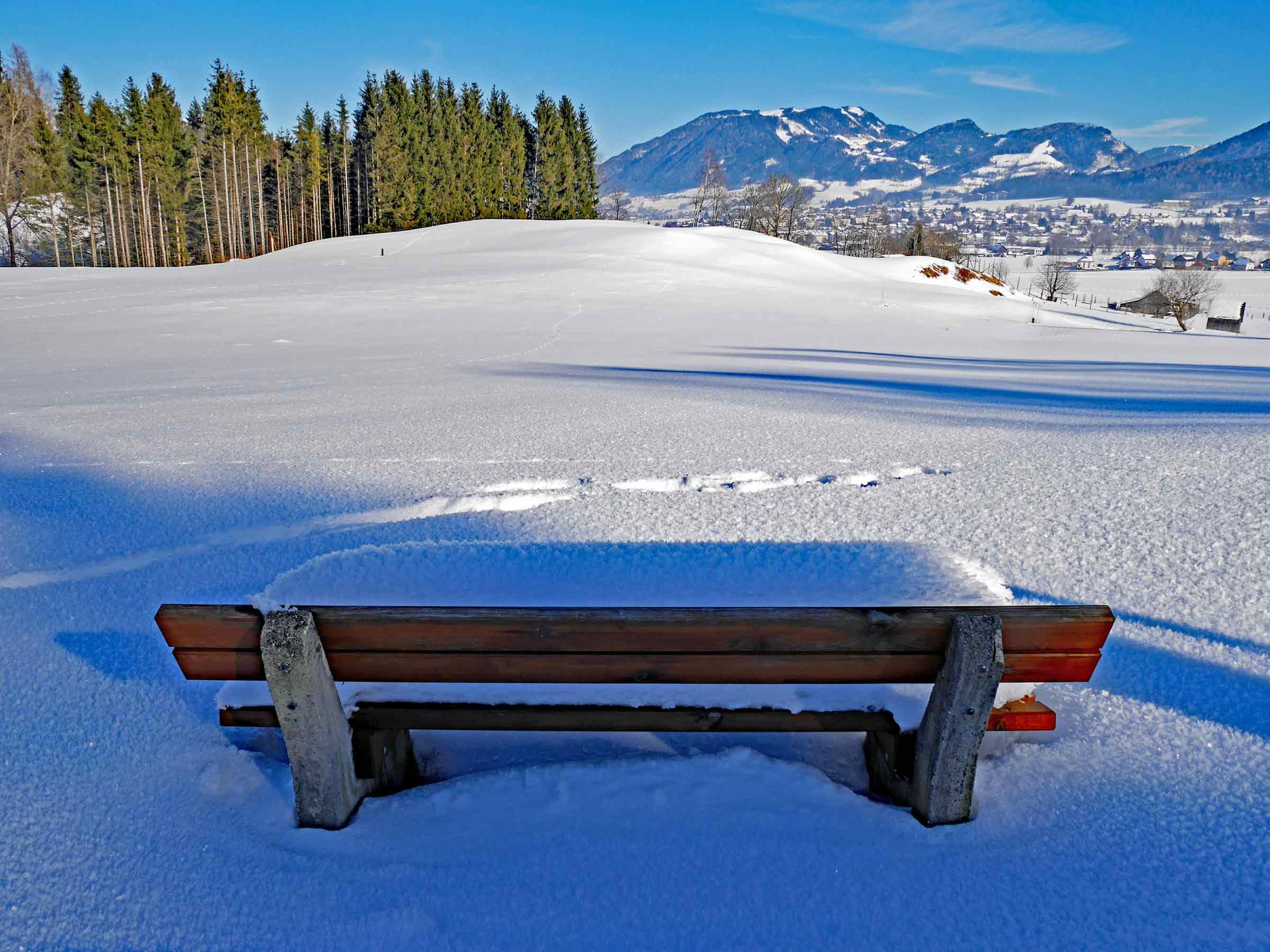 Warten, immer Warten. Schneebedeckt Bank in den Bergen bei blauem Himmel