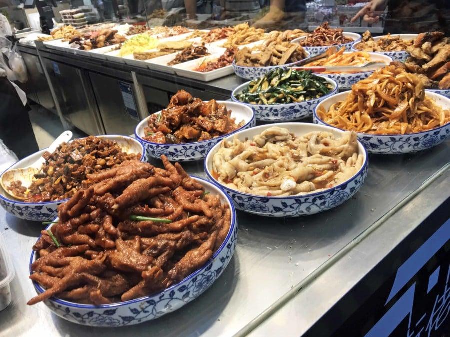 Enten- und Hühner-Füße ein beliebter Snack bei Einheimischen: Schalen mit verschiedenen chinesischen Gerichten