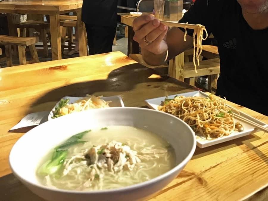 Essen in einem Foodcourt: Gebratene Nudeln und Nudelsuppe mit Hühnchen