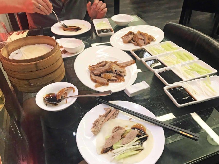 Gedeckter Tisch und Zubereitung des Wraps beim Peking Ente essen in China