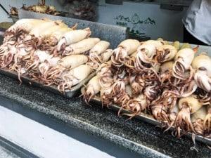 Street Food Gericht in China: Gefüllte Tintenfische, die gerillt werden