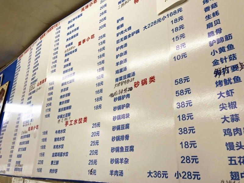 Chinesische Speisekarte in einem einfachen Restaurant in Peking. Schriftzeichen auf einer Tafel an der Wand