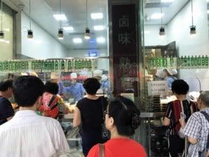 Einheimische warten vor einem typischen Street Food Laden für verschiedene Fleischsorten