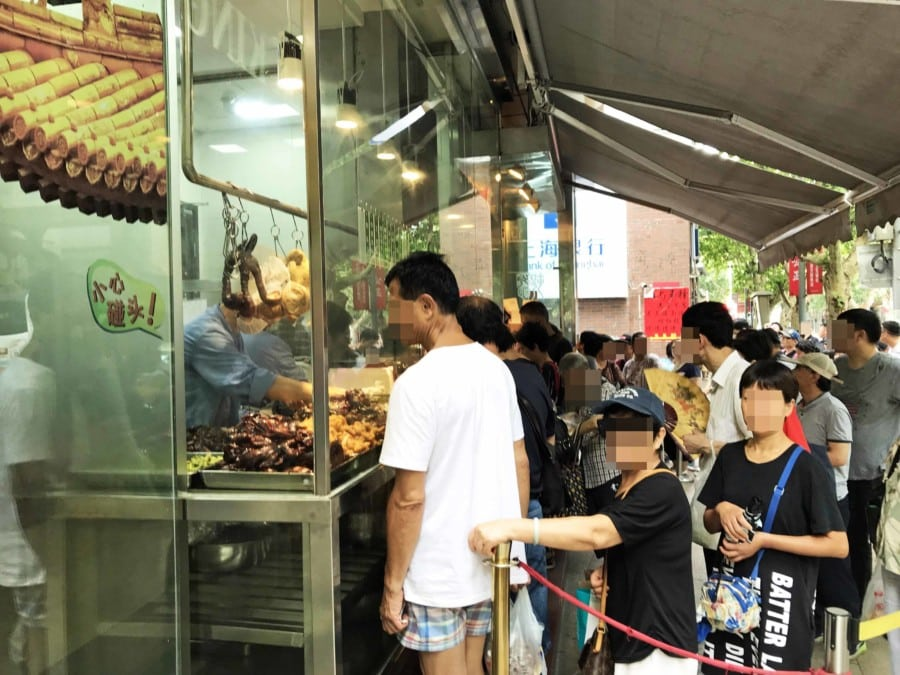 Typischer Street Food Laden für Enten- und Hühner-Füße. Eine Schlange von Einheimischen beim Warten