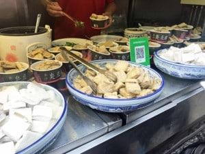Chinesischer Tofu. Verschiedene Schalen mit Tofu an einem Marktstand