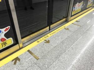 Fortbewegung in Peking: Pfeile auf dem Boden zeigen wie in der Metro in Peking aus- und eingestiegen wird