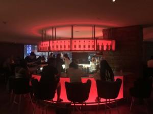 Aussichtspunkte Shanghai: 32. Stock der Vue Bar im Hyatt on the Bund. Blick auf die Bar im Inneren mit roter Beleuchtung und Menschen auf Barhockern