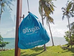 Verpackung des GlisGlis-Netzes: Farbiger Beutel an einem Fenster hängend mit Palmen im Hintergrund